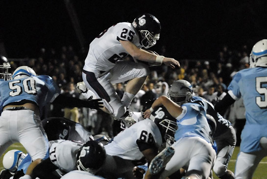 Whit Bissett (25) of Lake Oswego flies over the blocking of teammate Andre Lee (68) to score a one yard touchdown with 1:47 left in the third quarter to put the Lakers up 41-3.
