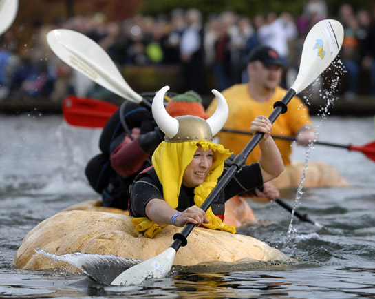 A contestant in the growers' race paddles her giant pumpkin in the spirit of the Vikings who are rumored to have crossed the Atlantic in the very same manner in the 18th century.