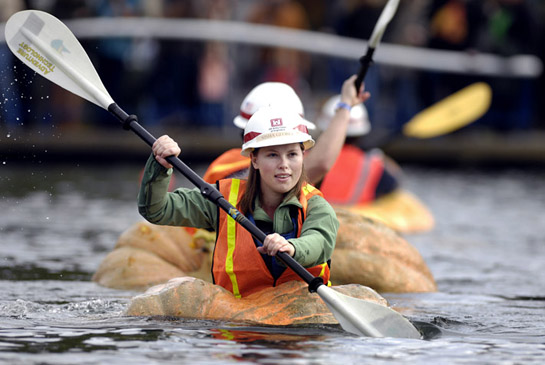 Nisha Georga of the U.S. Army Corps of Engineers paddles her way across the Lake at the Commons in Tualatin, Oregon as she and other corps members particpate in a challenge race against city of Tualatin employees.