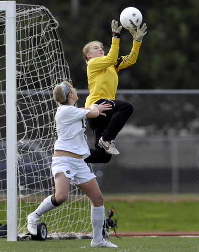 Sherwood goalkeeper Kassee Flint goes high to pull in a cross to foil a goal-scoring opportunity for Bend's Kelsey Corney.