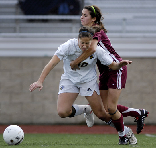Amelia Salazar (behind) of Sherwood resorts to fouling Bend's Daniela Solis (foreground) to prevent her from breaking into the attacking third.