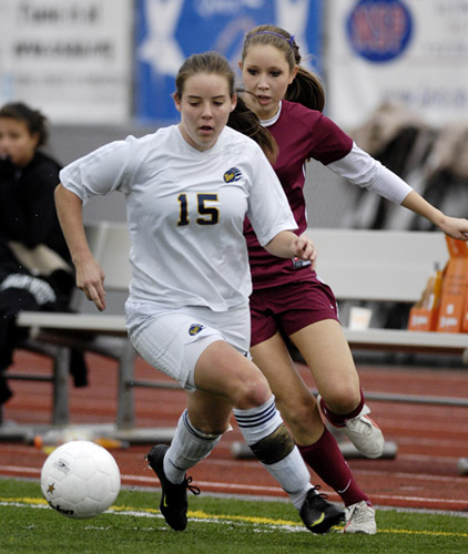 Kelsey Greene (left) of Bend beats Sherwood's Mallory Edmunson (right) down the left wing during a second half attack.