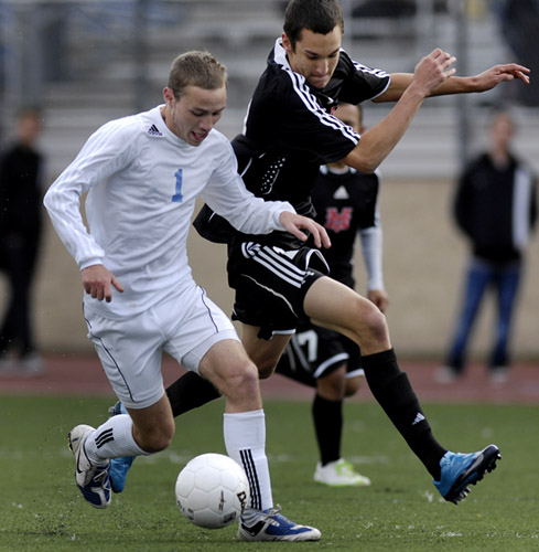 Brian Cronk (left) of Corvallis shields off the defense of Mt. View's Mike Wood (right) at he advances the ball through midfield.