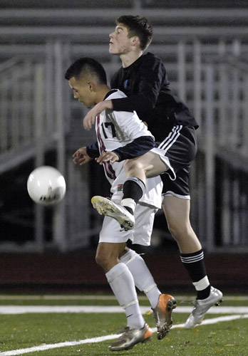 Brandon McPheeters (right) of Corvallis rides over the back of Glencoe's David Cazares (left) in an attempt to win possesion.  Cazares was able to bring the ball to his feet and evade the pressure of McPheeters.