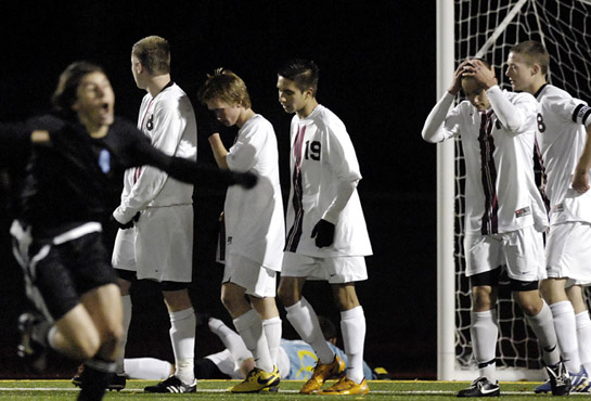 The Glencoe defense reacts after going down 0-2 as Corvallis goal-scorer Banner Schafer (in black) celebrates by sprinting to the stands after hitting a laser accurate 20 yard free kick.