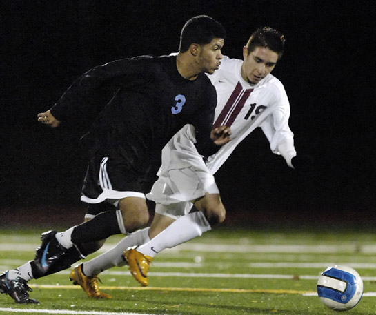 Andres Nieves-Bernal (left) of Corvallis looks for a pass upfield under pressure from Alan Portilla (right) of Glencoe.
