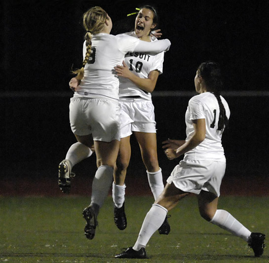 Kelli Crandall (left) and Sarah Bridges (center) of Jesuit embrace and leap into the air in celebration of Bridges' goal with 34:11 left in the match giving the Crusaders a 1-0 lead.  Teammate Emily Fellows (right) also joined in the celebration.