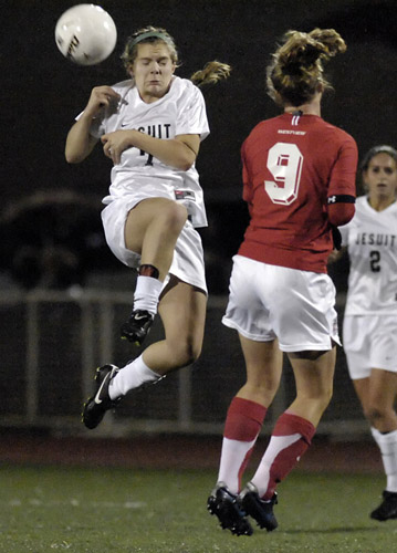 Rebe Wolverton (left) of Jesuit heads the ball past Westview's Amanda Minter during second half play.