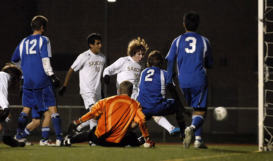 Ethan Jones (center in white) sticks away a rebound off a save by South Medford keeper Mitch North (in orange) to score the game winning goal for the Saxons with 13:45 left in the match.