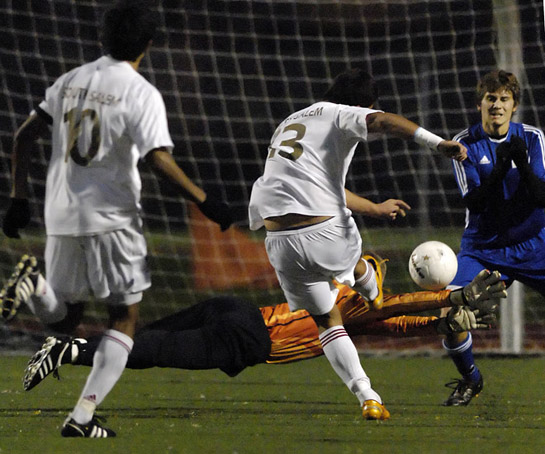 After recovering from a collision with South Salem's Pablo Ceja (13), South Medford goalkeeper Mitch North dives in a despirate attempt to block Ceja's shot onto an open net.  North could not get a hand on the ball but was saved by teammate Cody Anders who miraculously headed the ball wide of the post at the last second.