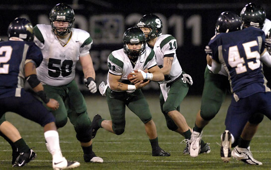 Sheldon offensive linemen Derek Nielson (left) and Jason Geiger (right) open a hole for Cameron Abeene as he receives the hand-off from quarterback Jordan Johnson on an eight yard gain for a first down early in the fourth quarter.