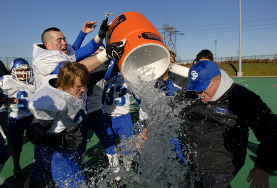 St. Paul head coach Tony Smith slips out from the cascading ice water as the Buckaroos begin celebrating their OSAA 1A State Football Championship after defeating Imbler 38-34.
