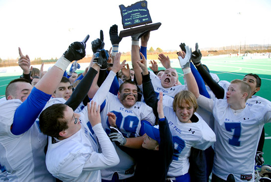 The St. Paul Buckaroos hoist the OSAA 1A Football Championship trophy high after defeating Imbler 38-34 for the state title.