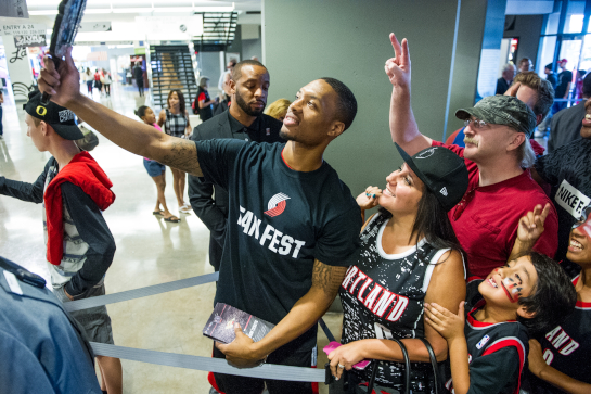 Portland Trailblazer guard Damian Lillard takes a selfie with fans as they enter the Moda Center for Fan Fest 2015.