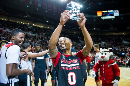 Damian Lillard (0) shares a humorous moment with Maurice Harkless (left) as he holds up the trophy he was presented as the MVP of the Fan Fest scrimmage.