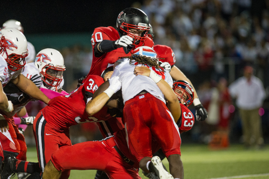 Clackamas defensive linemen Cole Loboy (33), Joe Leontyuk (36) and Devon Riddle (50) smother Centennial running back Jesse Porter (28) at the line of scrimmage during a first quarter drive.