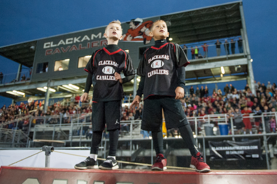 Two Clackamas ball boys stand atop the team bench to get a better view of the action during the Cavaliers' homecoming game against Centennial.