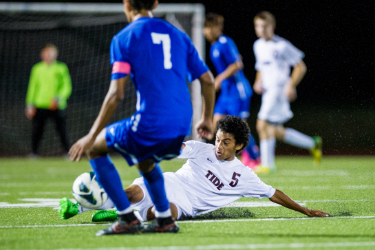 Glencoe midfielder Eddie Sauceda (5) slides to win a tackle against Hillsboro Sergio Aquilar (foreground) during the second half of the Tide's derby match against Hillsboro High at Hare Field in Hillsboro.