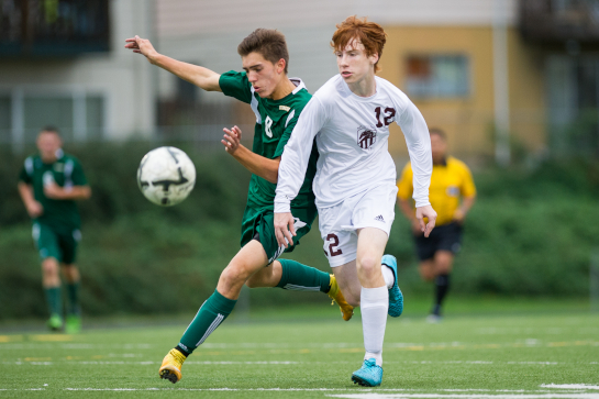 Even McClelland (12) of Milwaukie battle for a ball in midfield against Rex Putnam forward Tanner Ujifusa (8).