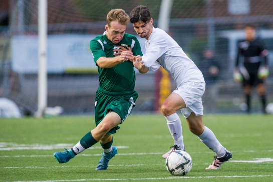 Devin Duval (7) of Milwaukie battles for a loose ball against Rex Putnam midfielder Garrett Benedict (3).