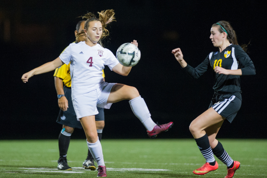 Milwaukie midfielder Ellie Holmes (4) battles for a loose ball under pressure from Rex Putnam midfielder Abigail Herbert (10).