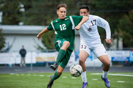 Rex Putnam midfielder Chris Taylor (12) dribbles the ball up the wing under pressure from Jerry Navarrete (17) of Milwaukie.