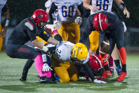 Oregon City defensive backs Tyler Dye (left) and Trevon Bradford (right) force a third quarter fumble by Barlow running back Jobadiah Malary (28) which is recovered by the Pioneers defensive end Brandon Dillon (36 not in picture).