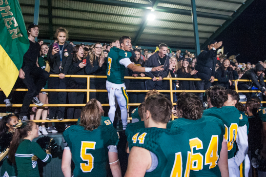 Rex Putnam quarterback Jake Hamilton leads the student section in signing the school fight song after an emotional victory 23-19 victory over local rival La Salle in the final minutes of the fourth quarter.