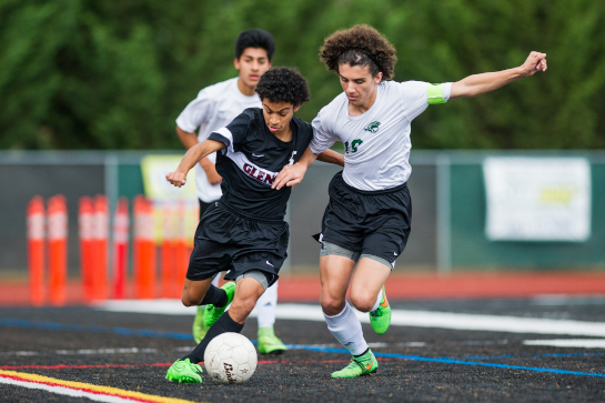 Glencoe midfielder Eddie Sauceda (left) dribbles down the right wing under pressure from West Salem midfielder Gabriel Linares (right) in the first half.